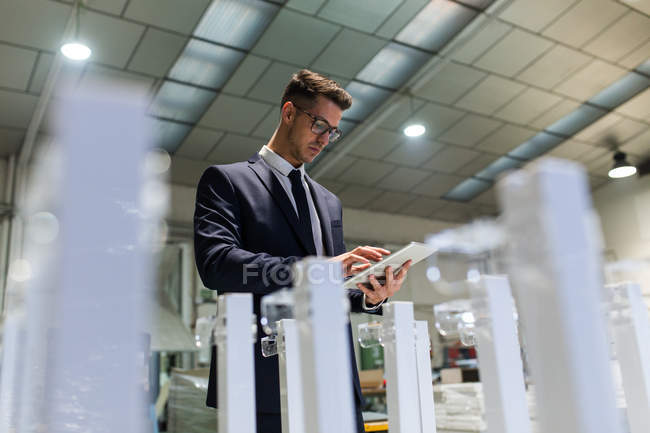 Young stylish man in elegant suit using tablet while controlling quality of factory maintenance. — Stock Photo