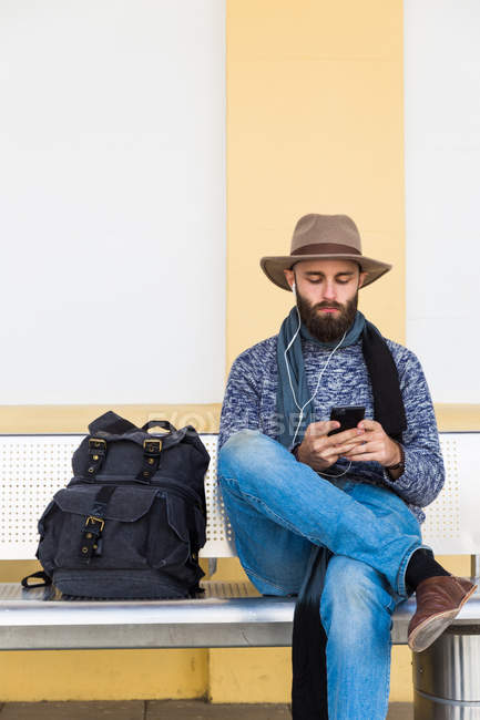 Bearded man with backpack sitting on bench and listening music with earphones while browsing smartphone — Stock Photo