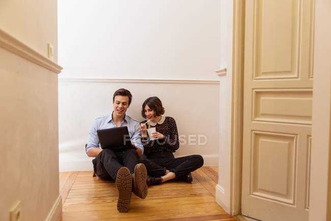 Young couple sitting on floor at home and using laptop while eating wok — Stock Photo
