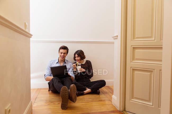 Jeune couple assis sur le plancher à la maison et l'utilisation ordinateur portable tout en mangeant wok — Photo de stock