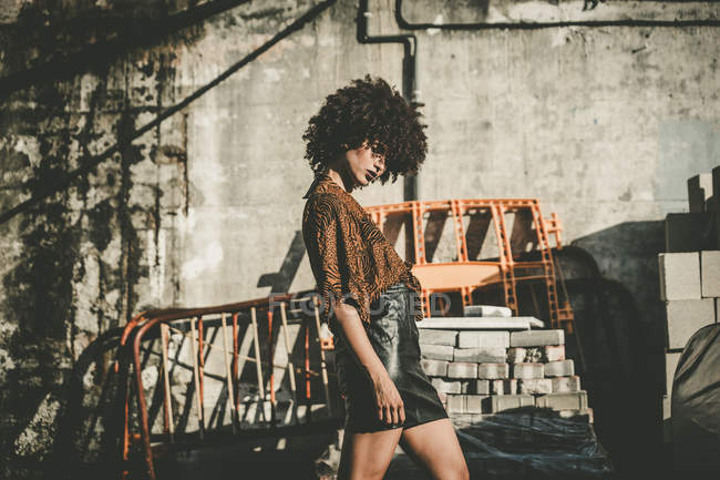 Young woman with afro wearing black leather skirt posing at construction plant — Stock Photo