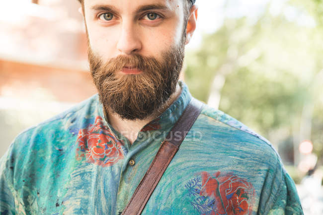Portrait of bearded man looking at camera at street scene — Stock Photo
