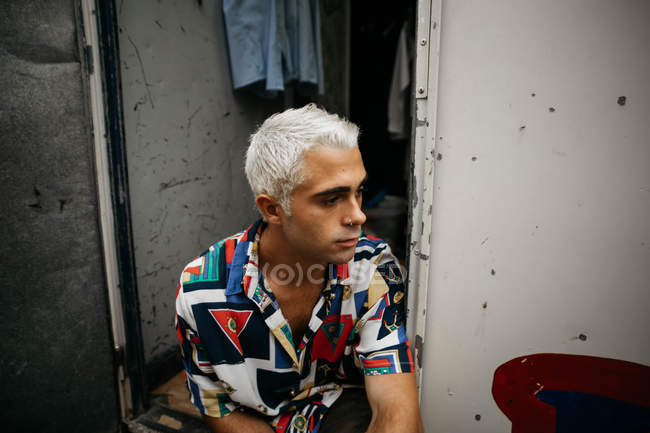 Man with bleached hair looking away — Stock Photo