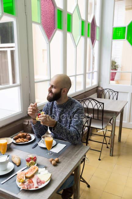 Портрет мужчины, сидя на стол завтрак и еда в бистро фруктовый салат — стоковое фото