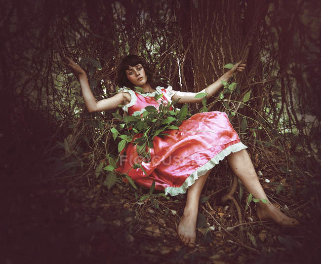 Woman wearing pink dress lying in bushes in forest. — Stock Photo