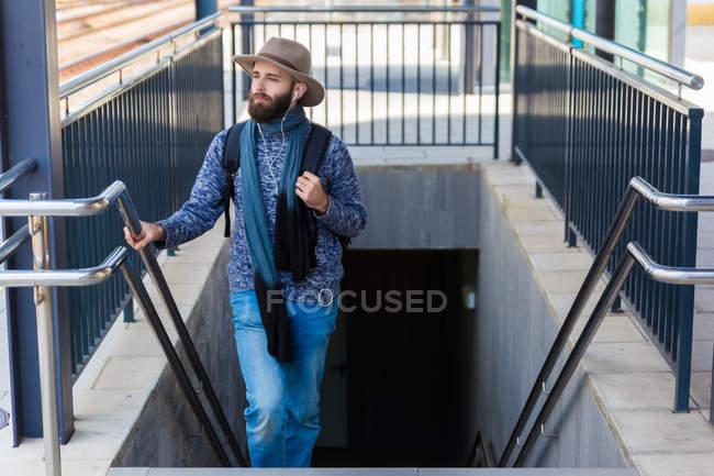 Vue de face de l'homme en remontant sur les escaliers de la station de métro et d'écouter de la musique. — Photo de stock
