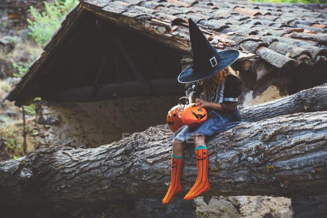 Girl in costume posing on tree — Stock Photo