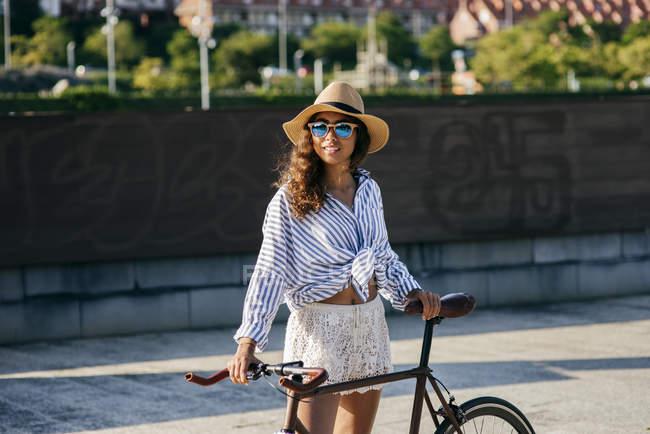 Chica en sombrero de pie con bicicleta - foto de stock