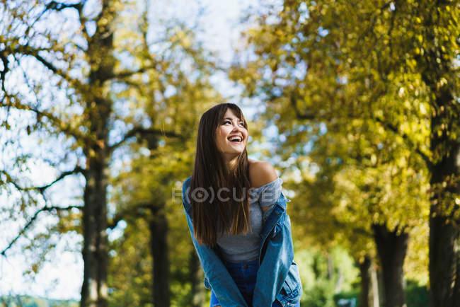 Mulher alegre rindo no parque e olhando para longe — Fotografia de Stock