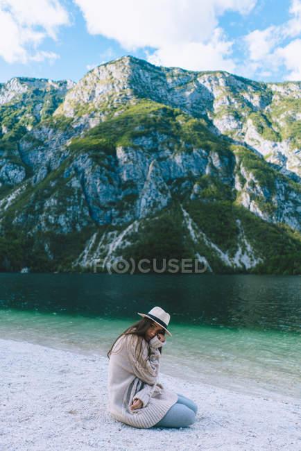 Menina de chapéu sentado margem do lago — Fotografia de Stock