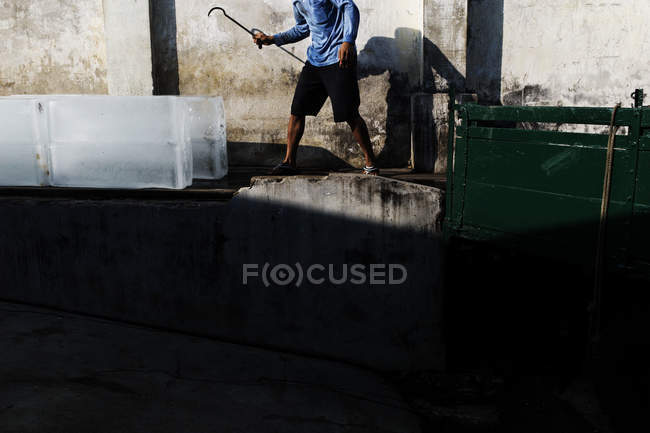 Crop image de l'homme portant des blocs de glace avec crochet sur la scène de la rue — Photo de stock