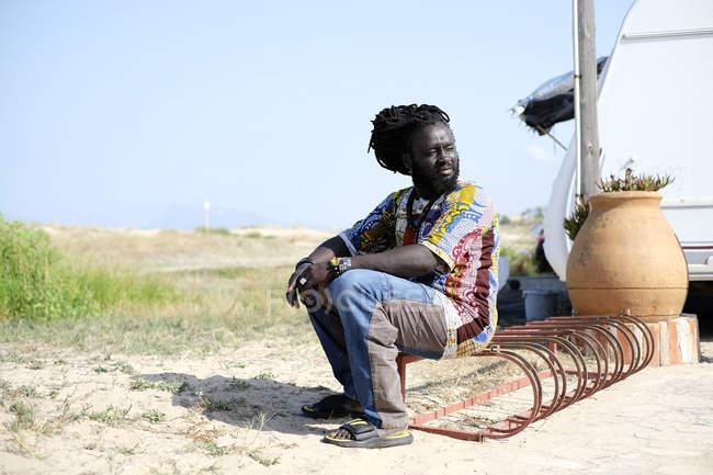 Black man sitting near trailer — Stock Photo
