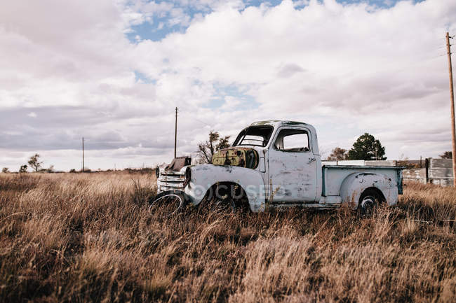 Old abandoned truck in dry field on cloudy day — Stock Photo