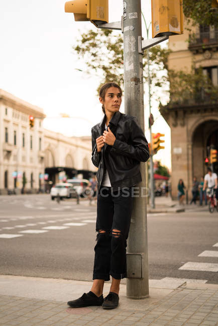 Full length portrait of boy leaning on traffic light post at street and looking aside — Stock Photo