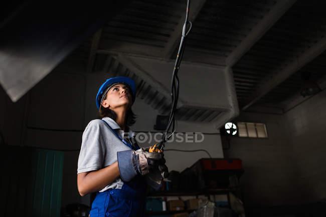 Retrato de ángulo bajo de mujer mecánico utiliza polipasto y mirando por encima de - foto de stock