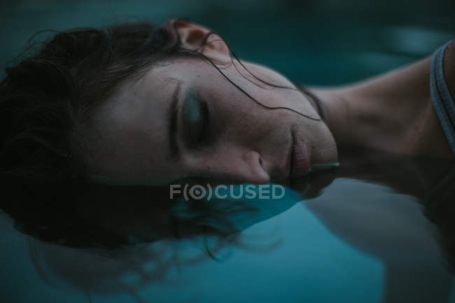 Half face of woman with eyes closed in water — Stock Photo
