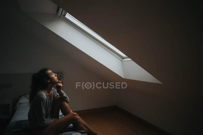 Брюнетка сидит на кровати у чердачного окна — стоковое фото