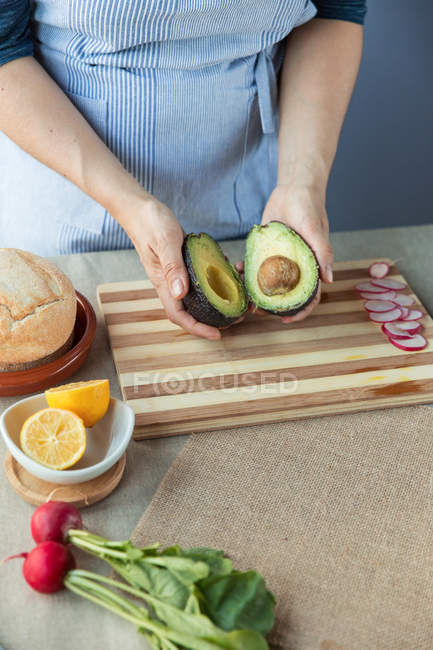 Cook holding avocado halves — Stock Photo