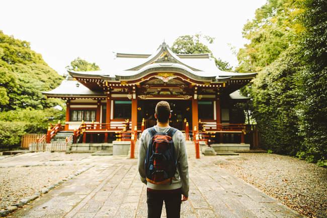 Rückansicht eines Mannes mit Rucksack, der am Tempel im asiatischen Stil steht. — Stockfoto