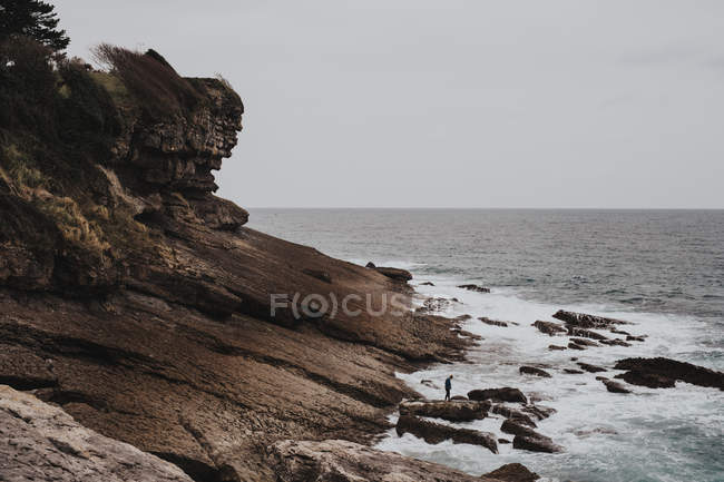 Distant view of traveler standing on coastal cliff — Stock Photo