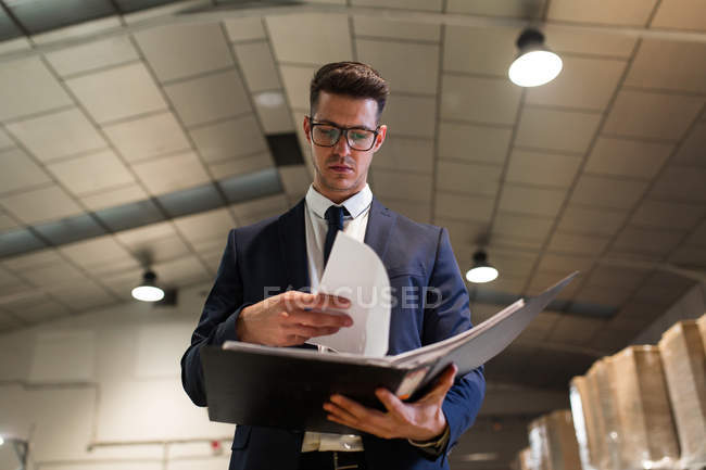 Elégant homme sérieux debout à la table de l'usine et la lecture de documents . — Photo de stock