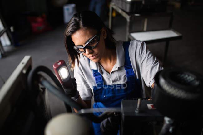 Vista de ángulo alto de motor de compresor Inspección mecánica femenina con linterna - foto de stock