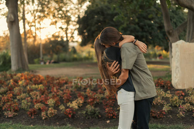 Вид сбоку на молодую пару, гуляющую в парке — стоковое фото