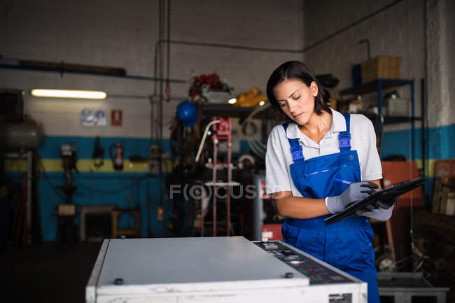 Female mechanic with clipboard checking machine status — Stock Photo
