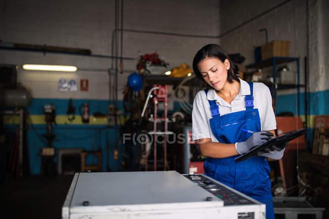 Mujer mecánico con portapapeles comprobación estado de la máquina - foto de stock