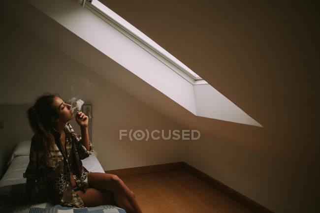 Joven morena fumando cigarrillo mientras está sentada en la cama contra la ventana del ático - foto de stock