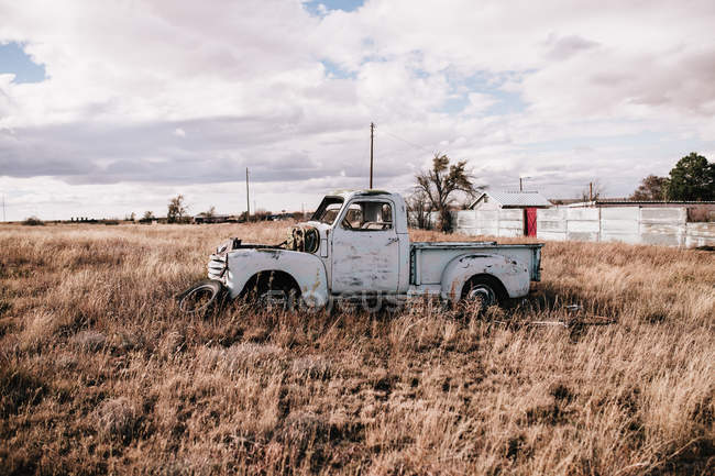 Old abandoned truck in arid field on cloudy day — Stock Photo