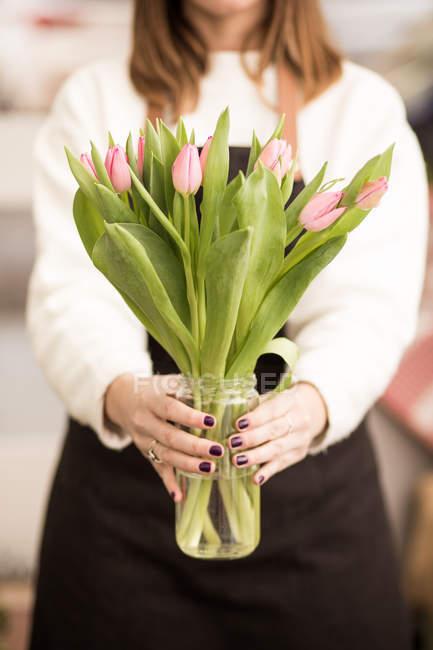 Женщина держит свежие розовые тюльпаны в банке — стоковое фото