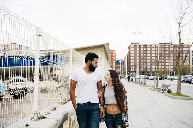 Encantadora pareja caminando por la calle - foto de stock