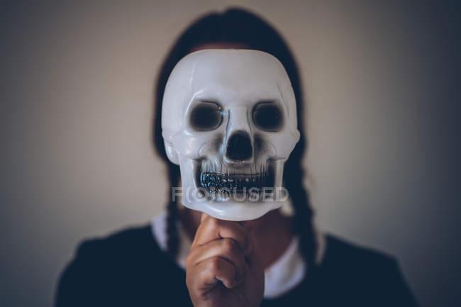 Porträt eines unkenntlichen Mädchens in schwarzem Kleid mit Totenkopfmaske vor dem Gesicht. — Stockfoto