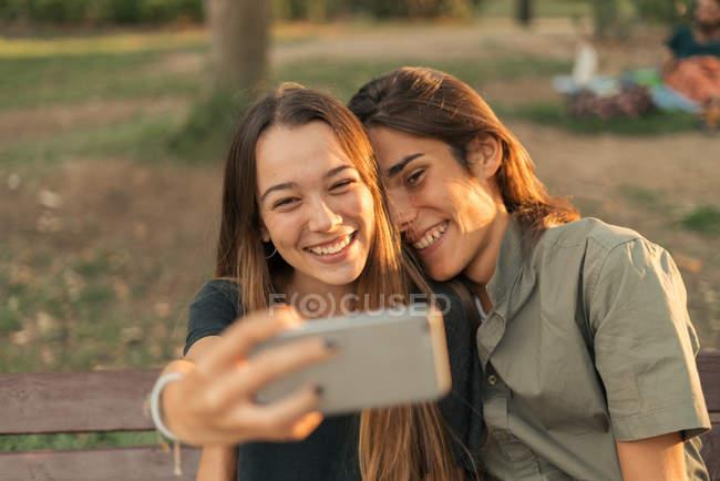 Porträt der jungen lächelnde paar nehmen Selfie mit smartphone — Stockfoto