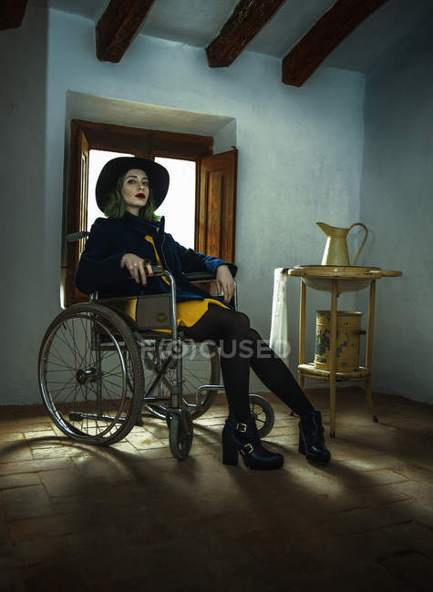 Young woman sitting in wheelchair and looking at camera against window — Stock Photo