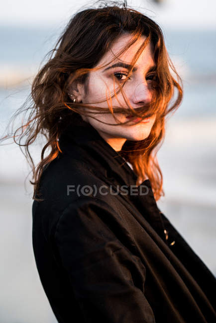 Portrait of young sunlit woman looking at camera — Stock Photo