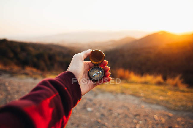 Crop hand of person standing in hills and holding compass. — Foto stock