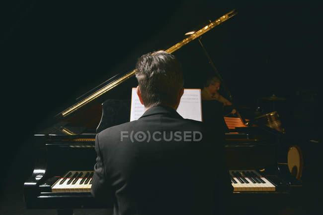 Vista trasera del hombre con chaqueta tocando el piano - foto de stock