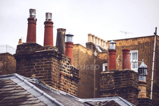 Camini In Mattoni Rossi : Camini in mattoni rossi sui tetti contro cielo blu u foto stock