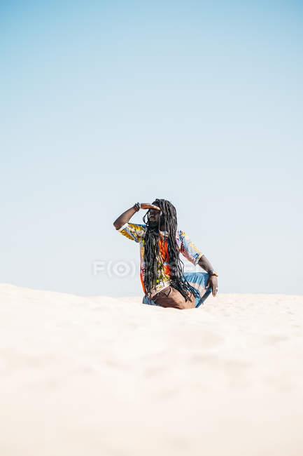Hombre en la arena mirando hacia otro lado - foto de stock