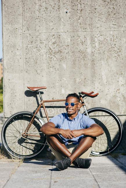 Hombre con gafas de sol sentado cerca de la bicicleta - foto de stock
