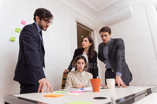 Gruppe von jungen Kolleginnen und Kollegen mit Gespräch Fragen arbeiten in Büro — Stockfoto