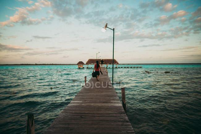 Задній вид мандрівника, ходьба на Пірс над морський пейзаж — стокове фото