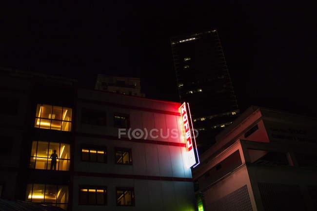 Niedrigen Winkel Ansicht der Hotelgebäude mit Leuchtreklame und Silhouette im Fenster — Stockfoto