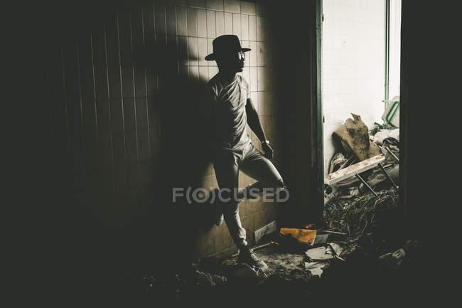 Elegante hombre apoyado en la pared en la habitación con montones de basura . - foto de stock