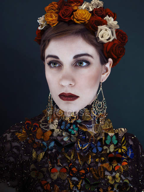 Woman with flowers in hair wearing dress made with butterflies. — Stock Photo
