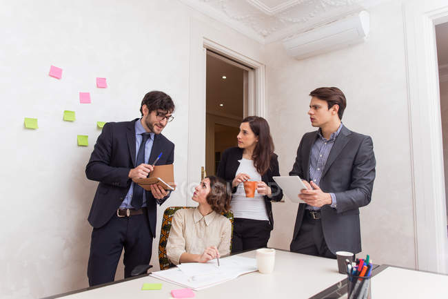 Команда молодых коллег, обсуждают рабочие вопросы в офисе — стоковое фото