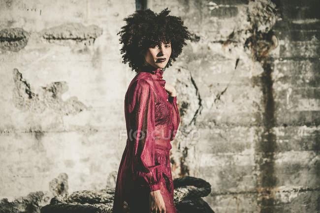 Ragazza riccia in abito rosso posa sopra muro squallido — Foto stock