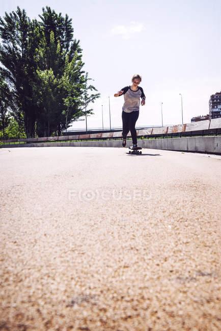 Skateboarder femme équitation skate au parc — Photo de stock